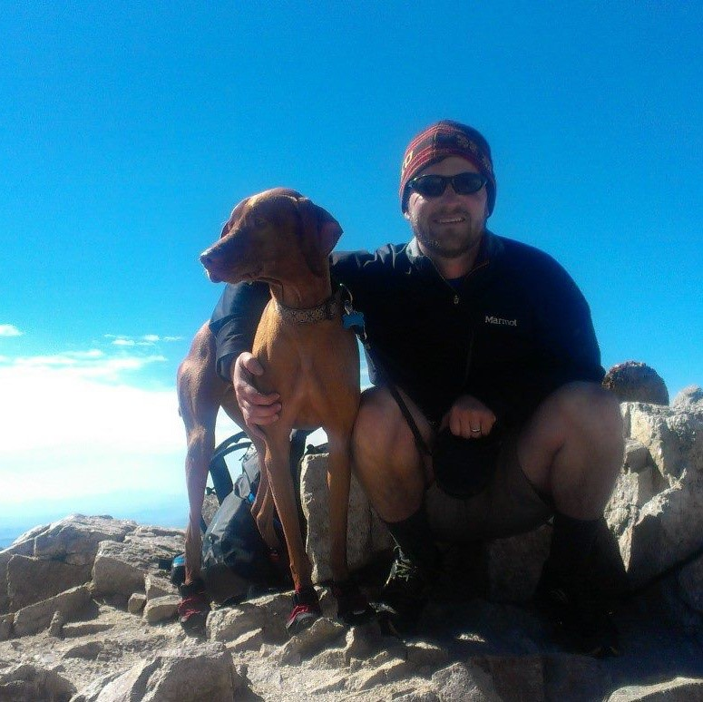 Chuck at mountain summit with dog